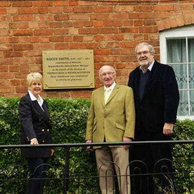 Standing by the commemorative wall plaque to Roger Smith outside the Warwick almshouses are (left to right) Thelma Atkins, chairman of the almshouses sub-committee of the Thomas Oken Trust; Alan Sturley and Terry Brown
